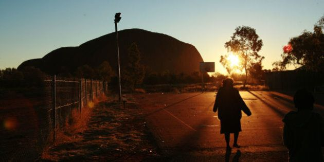A child plays at sunset in the Aboriginal community of Mutitjulu, in the shadow of Uluru, in the Northern Territory. The town is the first to be targeted in the Australian government's campaign to stamp out child abuse in remote indigenous communities. Australian Prime Minister John Howard says the permit system in the Northern Territory restricting entry to such communities had kept them 'out of view and out of mind', hindering efforts to tackle their problems, 26 June 2007. (Photo by Jason South/The AGE/Fairfax Media via Getty Images)