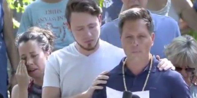 Don Damond, with son Zach, delivers a prepared statement outside the family home in south