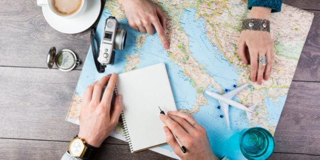 Two young people together planning trip to Europe. Top view. empty white space in notebook where you...