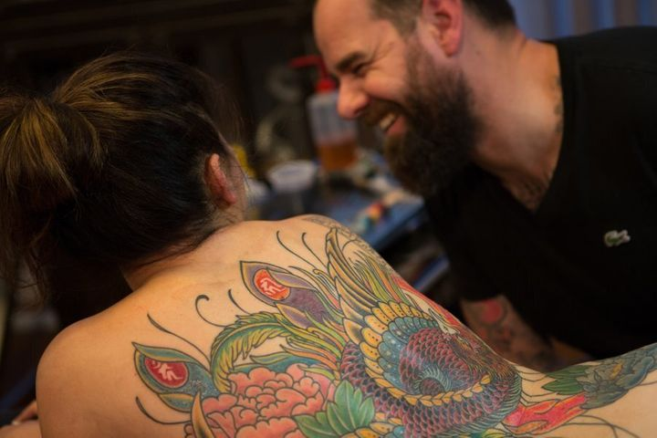 "Kian Forrea, tattoo artist and founder of Authentink ""vibing"" with a client."