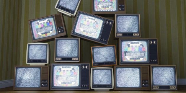 Group of many vintage old televisions stacked and piled up like a pyramid and a interior background showing...