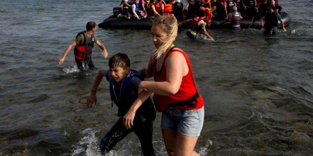 A volunteer helps a Syrian boy as he arrives with others at the coast on a dinghy after crossing from...