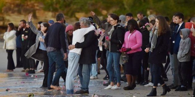 Justine Damond's parents John and Maryan Ruszczyk hug at the shore of Sydney's Freshwater Beach.