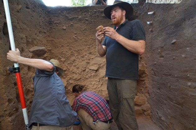Dig leader Chris Clarkson examining a stone tool in the dig