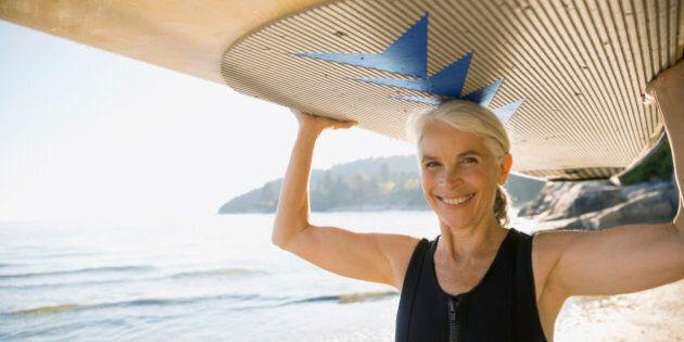 Senior woman holding paddle board overhead on