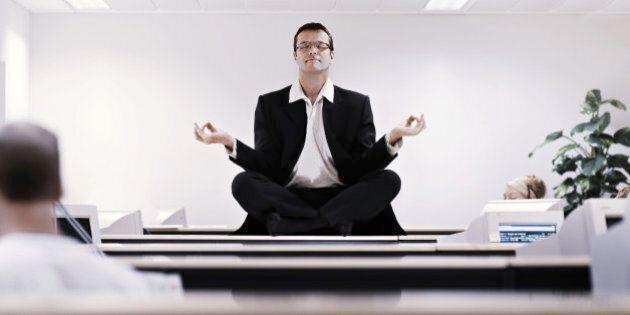 Businessman meditating on office