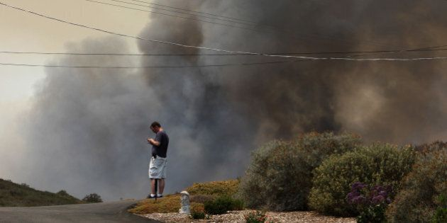 SAN MARCOS, CA - MAY 15:  A resident looks at his phone as smoke from the southeast flank of the Cocos fire bears down on houses near Del Dios Highway on May 15, 2014 near San Marcos, California. Fire agencies throughout the state are scrambling to prepare for what is expected to be a dangerous year of wildfires in this third year of extreme drought in California.   (Photo by David McNew/Getty Images)