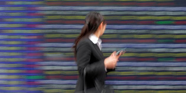 A woman walks past the electronic stock board of a securities firm in Tokyo Wednesday, June 6, 2012....