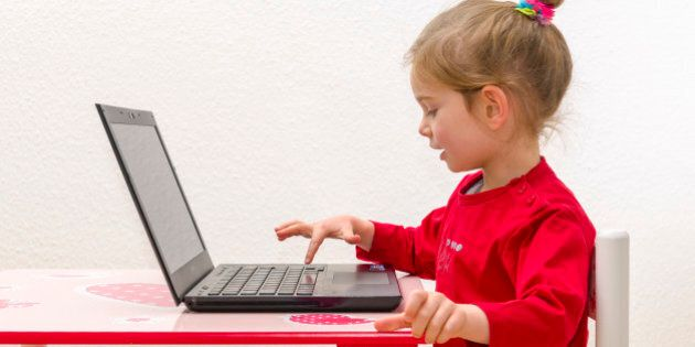 WUERZBURG, BAVARIA, GERMANY - 2014/12/21: A blond three year old girl is sitting in front of a notebook,...