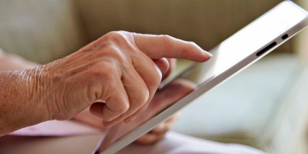 Elderly woman, aged 77, using tablet computer to look at photos in a private retirement