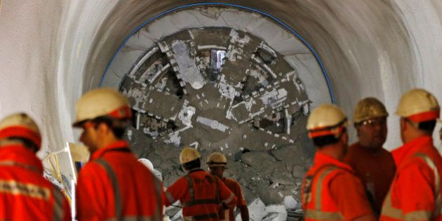 Crossrail workers stand, backdropped by a thousand tonne tunnelling machine, after it breaks through...