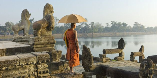 Cambodia, Siem Reap, Angkor Wat, Sras Srang, Buddhist monk standing next to stone carvings and lake.