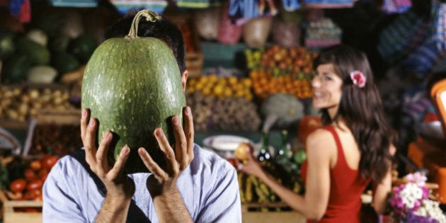 Man Stands by a Market Stall Holding a Watermelon in Front of His