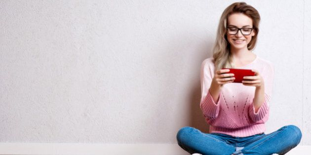 Happy beautiful woman sitting on the floor and using smartphone