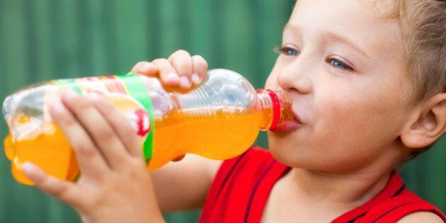 Boy drinking unhealthy bottled soda