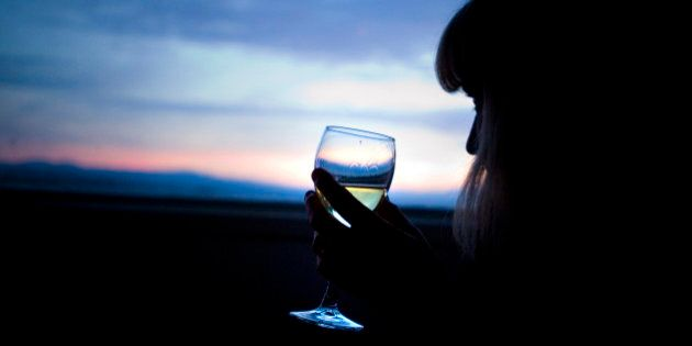 A woman drinks a glass of wine and watches the sunset over Lake Taupo, New Zealand.
