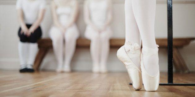Female ballet dancer performing point work in front of peers in dance