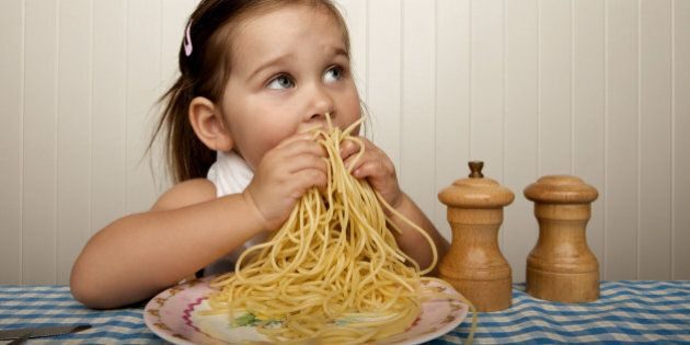 Little girl eating spaghetti with her