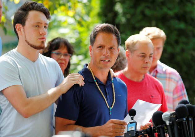 Don Damond is comforted by his son Zach Damond as he speaks to the media about his fiance, Justine Damond...