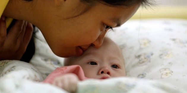 Gammy, a baby born with Down's Syndrome, is kissed by his surrogate mother Pattaramon Janbua at a hospital...