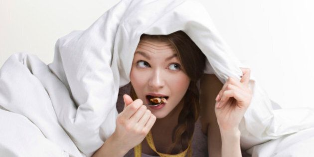 young beauty woman eating dessert under cover on white