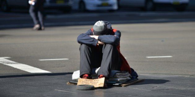 A homeless man sits on a street in the Central Business District of Sydney as the Australian government...