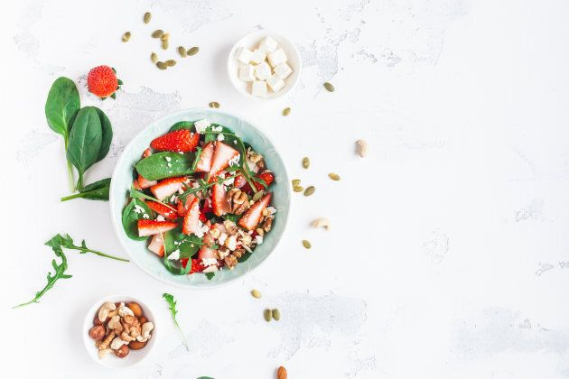 Strawberry salad. Spinach leaves, sliced strawberries, nuts, feta cheese on white background. Healthy food concept. Fat lay,