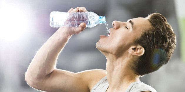 Thirsty young man drinking water after