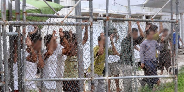 Asylum-seekers look through a fence at the Manus Island detention