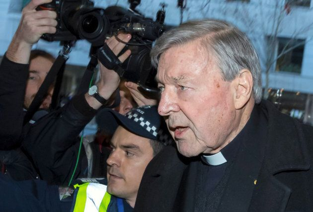 Cardinal George Pell is surrounded by police and members of the media as he arrives at the Melbourne...
