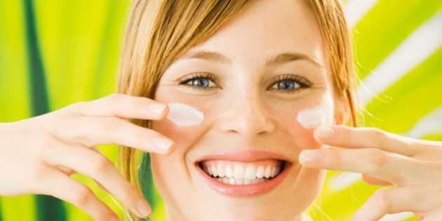 Young woman putting cream on face, smiling,