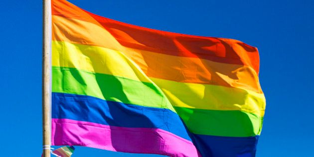 Rainbow flag against sky during gay pride