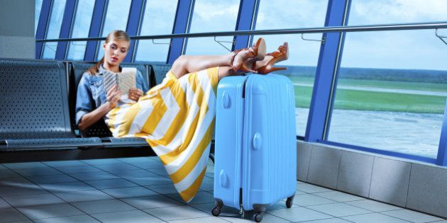 Young adult woman waiting for her flight at the airport lounge and watching boarding pass.
