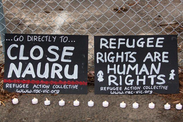 Banners and candles at the gates of a refugee detention centre during a candlelight vigil as protestors...