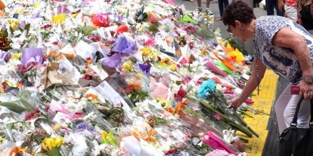 A woman places a floral tribute at a temporary memorial site close to the Lindt Chocolat Cafe in Sydney,...