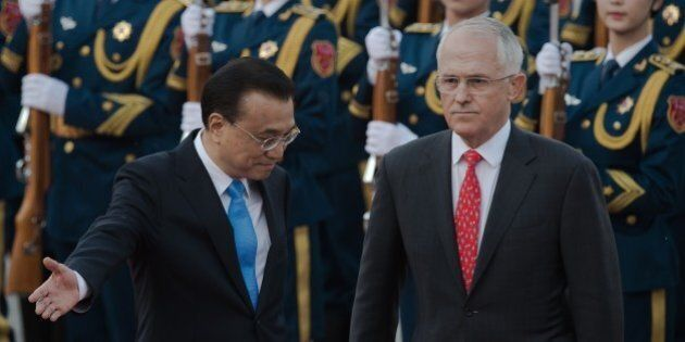 Australian Prime Minister Malcolm Turnbull (R) reviews a military honour guard with Chinese Premier Li...