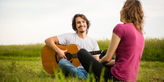 Young man playing guitar to his girlfriend in nature - dating