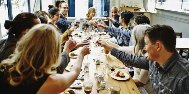 Smiling group of friends toasting at dinner party in