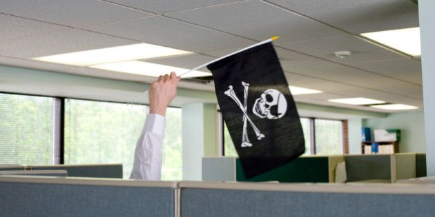 Businessman waving jolly roger flag cubicle
