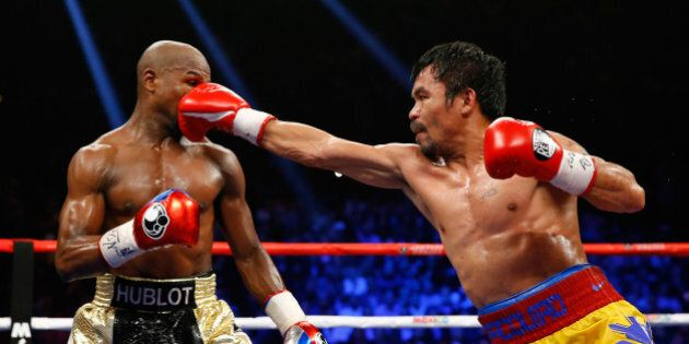 LAS VEGAS, NV - MAY 02: Manny Pacquiao throws a right at Floyd Mayweather Jr. during their welterweight...