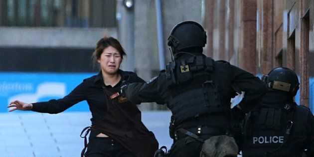 FILE - In this Dec. 15, 2014 file photo, Bae Jie-un, a staff member of a Sydney cafe and one of the hostages, runs to armed tactical response police officers for safety after she escaped from a cafe under siege in Sydney, Australia. Bae and her colleague told Seven Network television in paid interviews broadcast Sunday, Feb. 8, 2015, how Bae quietly unbolted an internal door to escape the cafe without gunman Man Horan Monis noticing.(AP Photo/Rob Griffith, File)