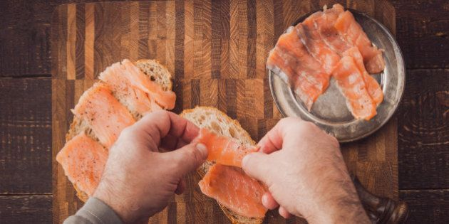 Cooking sandwiches with salmon on the wooden table top