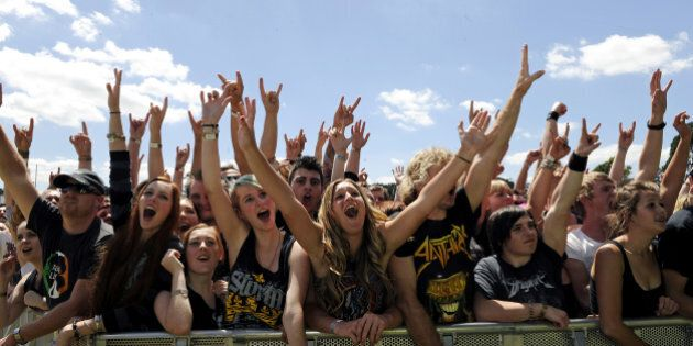 MELBOURNE, AUSTRALIA - MARCH 01: The front rows of the audience raise their arms and cheer in the sunshine...