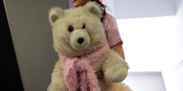 A member of the group Sa.weet carries a teddy bear backstage while waiting to perform at the Portuguese...