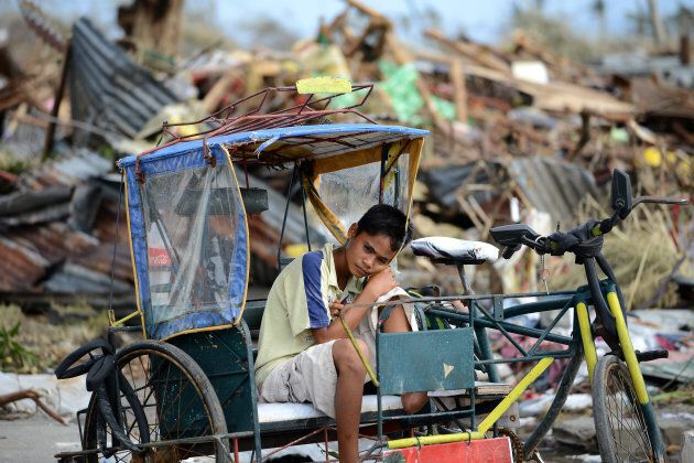 A young survivor surrounded by debris caused by Super Typhoon Haiyan in Tacloban in the eastern Philippine...