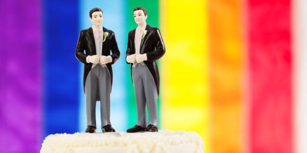 Subject: Same sex marriage wedding cake with two male groom figurine cake toppers and rainbow flag in