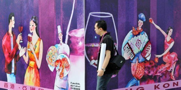 A man walks past a billboard advertising the upcoming Hong Kong Wine and Dine Festival in Hong Kong on...