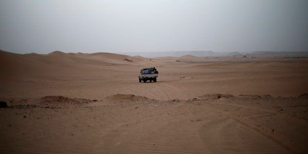 A vehicle transporting a group of African migrants drives through the desert on their journey from Ghat in southwest Libya May 29, 2014. A smuggler was transporting a group of African migrants through the desert to northern Libya. Libya's southwestern tip in the Sahara bordering Algeria and Niger has turned into an open door for illegal migrants from sub-Saharan countries heading for Europe, with the chaotic government in Tripoli appearing to have abandoned all control. The revolt that overthrew Libyan leader Muammar Gaddafi three years ago emptied Libya's arsenals, flooded the region with guns and dismantled much of the state apparatus, giving well-organised smuggler networks the run of the border. Border officials say up to 200 Africans cross the Ghat border strip every day, most headed north to the Mediterranean coast for the onward trip to Europe by boat. Picture taken May 29, 2014. REUTERS/Ahmed Jadallah (LIBYA - Tags: SOCIETY POLITICS IMMIGRATION)ATTENTION EDITORS: PICTURE 17 OF 31 FOR PACKAGE 'MIGRANT FLIGHT THROUGH LIBYA'TO FIND ALL IMAGES SEARCH 'JADALLAH GHAT'