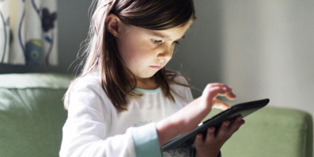 A young girl uses a tablet computer late at night with the glow from the screen on her