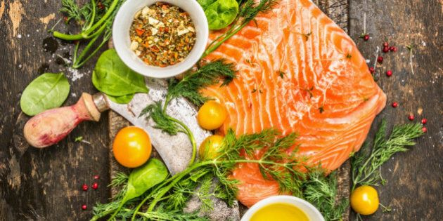 fresh salmon fillet with fresh healthy herbs,vegetables, oil and spices on rustic wooden background,...